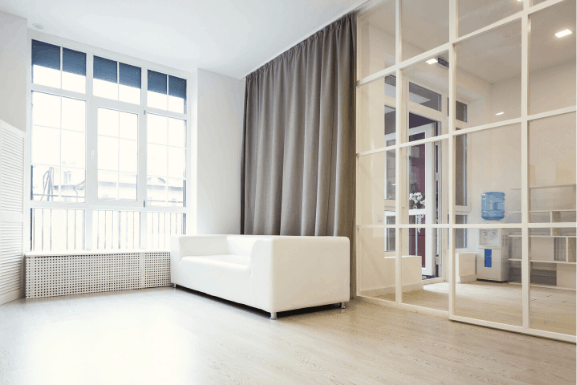 soundproof room divider curtain behind a sofa, covering from ceiling to floor. Grey color and completely blackout Sound proof wall divider and sound blocking, sound absorbing properties