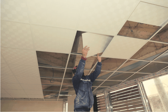 Man installing tiles on a suspended ceiling