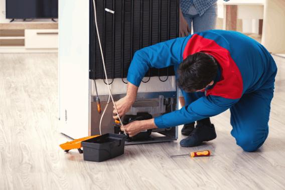 Man fixing a fridge's compressor